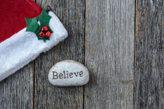 Santa Hat with the text Believe on a Stone Rock Stock Photos