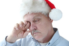 Santa hat on tired senior man Royalty Free Stock Photo