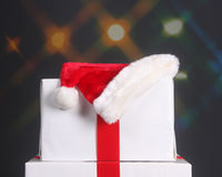 Santa hat on top of Christmas presents. Elegantly wrapped Christmas presents with a Santa hat on top set against a festive holiday background Stock Photo