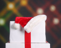 Santa hat on top of Christmas presents. Elegantly wrapped Christmas presents with a Santa hat on top set against a festive holiday background Royalty Free Stock Photos