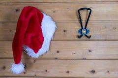 Santa Hat vermelha colorida que pendura em uma parede Fotografia de Stock