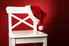 Santa hat on white chair front of red background Stock Photos