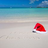 Santa Hat on white sandy beach and Merry Christmas Royalty Free Stock Photos