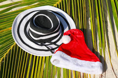 Santa hat and woman hat on palm leaf Royalty Free Stock Photography
