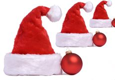 Santa hats. 3 santa hats isolated on white with a red christmas bulbs Stock Photography
