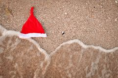 Santa hats on sandy beach - concept of New Year family holiday with the children on the sea. stock photo