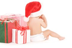 Santa helper baby with christmas gifts. Over white royalty free stock photos