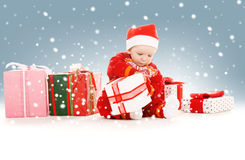 Santa helper baby with christmas gifts Stock Photos