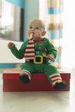 Santa helper baby with red gift Stock Images