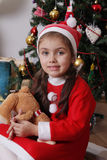 Santa helper with bear under Christmas tree Royalty Free Stock Images