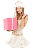 Santa helper in corset and skirt with pink gift. Santa helper blond in corset and skirt with pink gift box stock image