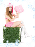 Santa helper with gift box on green cube. Sexy santa helper with gift box on green cube Stock Photos