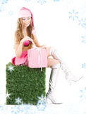 Santa helper with gift box on green cube Royalty Free Stock Image