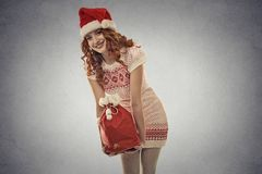 Santa helper girl carrying big red christmas sack full of gifts Royalty Free Stock Photos