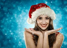 Santa helper girl. Closeup of beautiful Santa girl in red costume Royalty Free Stock Photo