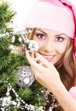 Santa helper girl decorating christmas tree Royalty Free Stock Photo
