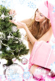 Santa helper girl decorating christmas tree Stock Photo