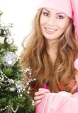 Santa helper girl with gift box and christmas tree Stock Photos