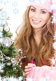 Santa helper girl with gift box and christmas tree Royalty Free Stock Photo