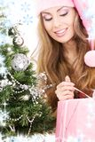 Santa helper girl with gift box and christmas tree Stock Photography