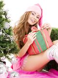 Santa helper girl with gift box and christmas tree Royalty Free Stock Images