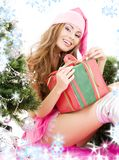 Santa helper girl with gift box and christmas tree Stock Photo