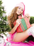 Santa helper girl with gift box and christmas tree Stock Image