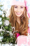 Santa helper girl with gift box and christmas tree Royalty Free Stock Photography