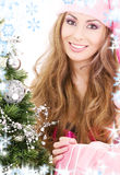 Santa helper girl with gift box and christmas tree Stock Images