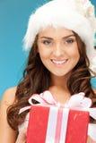 Santa helper girl with gift box Stock Photo