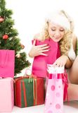 Santa helper girl with gifts and christmas tree. Lovely santa helper girl with gifts and christmas tree Stock Images