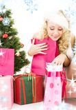 Santa helper girl with gifts and christmas tree Royalty Free Stock Photos