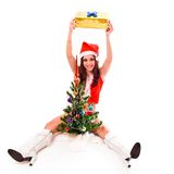 Santa helper girl holding a gift box. Behind tree over white Stock Photography