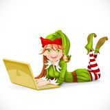 Santa helper girl lies behind the notebook Royalty Free Stock Photography