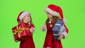 Santa helper are holding boxes with gifts and showing a thumbs up. Green screen. Children in colorful suits are holding boxes with gifts and showing a thumbs up stock video footage