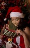 Santa helper looking inside Christmas sock stock images