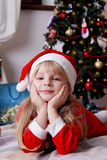 Santa helper lying under Christmas tree Royalty Free Stock Images