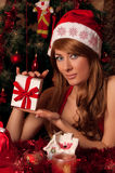 Santa helper with present under Christmas tree Stock Photo