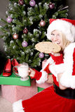 Santa helper by tree having a snack Royalty Free Stock Photography