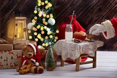 Santa is here. Santa`s hand taking a cookie from little table standing in the room with christmas tree and gift boxes around it Stock Photos