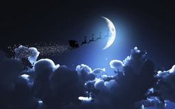 Santa and his sleigh flying in a moonlit sky Royalty Free Stock Images