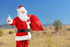 Santa hitchhiking on an open road Stock Image