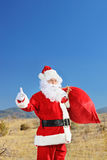 Santa hitchhiking outdoors with bag of presents Stock Image