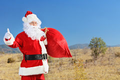 Santa holding a bag of presents and hitchhiking outdoors Royalty Free Stock Photography