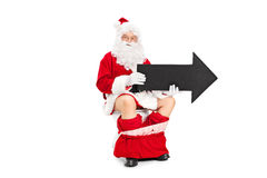 Santa holding black arrow seated on a toilet. Santa Claus holding a big black arrow seated on a toilet isolated on white background royalty free stock photography