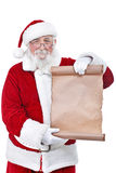 Santa holding blank scroll list. Traditional Santa Claus with a paper scroll, isolated on white background stock photo