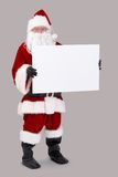Santa holding blank white board. Full size portrait of Santa holding blank white board, looking at camera, isolated on gray background Royalty Free Stock Images