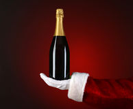 Santa Holding Champagne Bottle in Palm Stock Photo