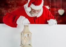 Santa holding christmas lantern and looking down Stock Images