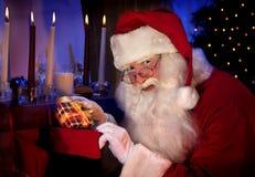 Santa Holding Christmas Present en sus manos Imágenes de archivo libres de regalías